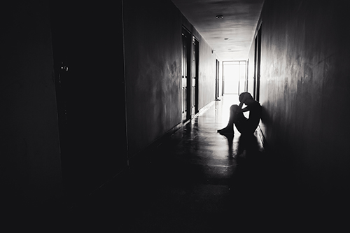 sad person sitting in a corridor black and white photo