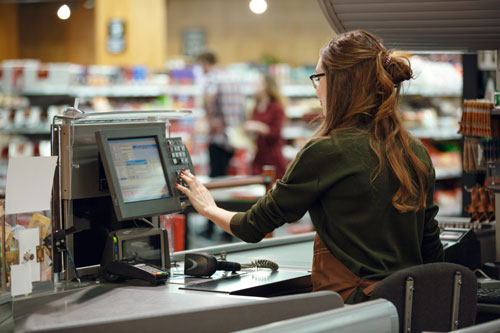 A woman sits at a cash register in a supermarket.