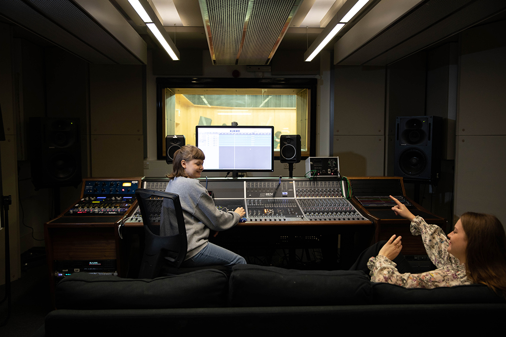 Two female undergraduate students using music studios onlooking the performance space