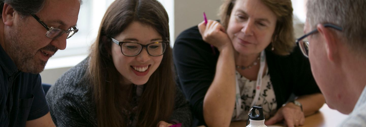 Creative writing students around a table smiling