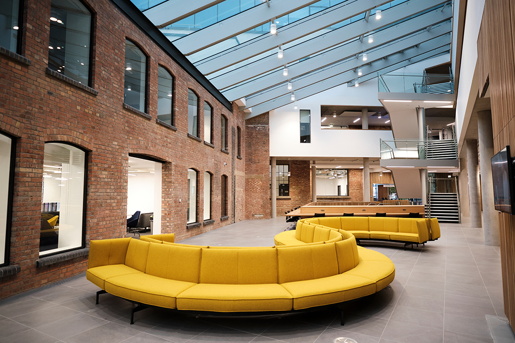 Interior of The City Law School with curved yellow sofa by staircase
