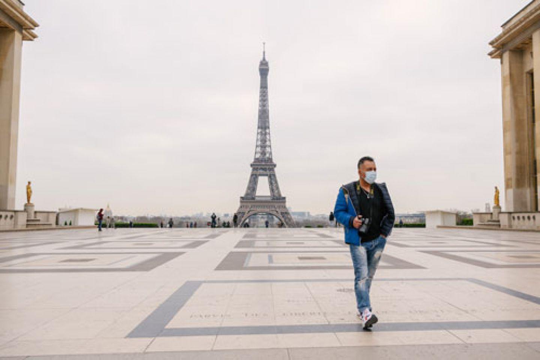 Man walking in Paris wearing facemask