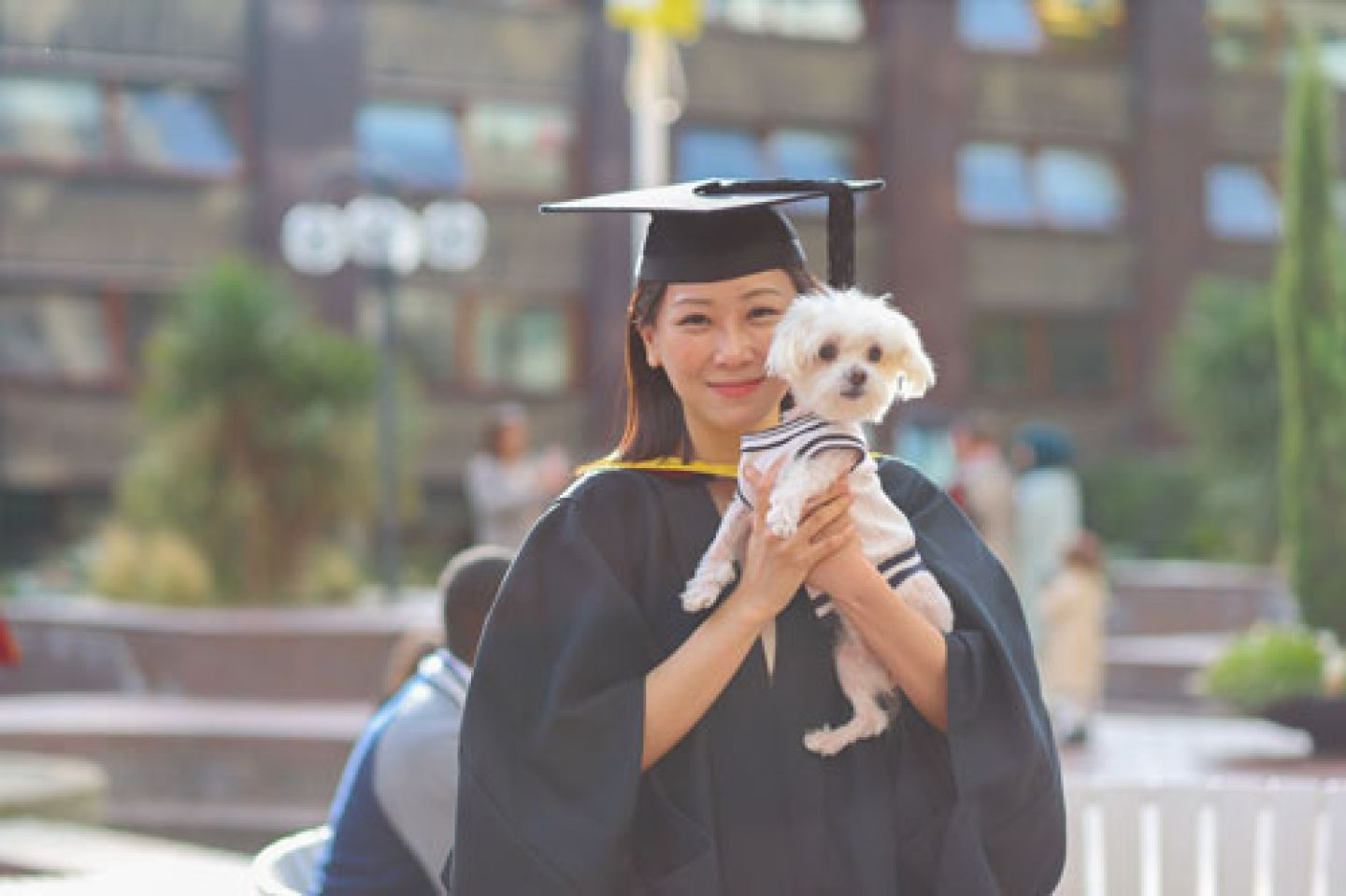 Female graduate shares her proud moment with her pet dog.