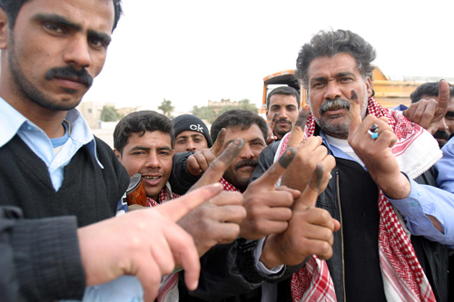 Iraqi police show their ink-stained index fingers