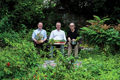 Three people in a lush garden