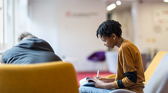 A female student writing in a communal area
