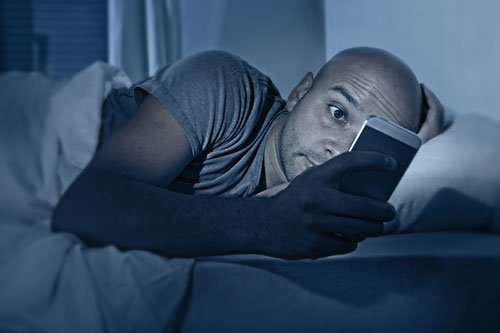 Young man looks at his smart phone in bed