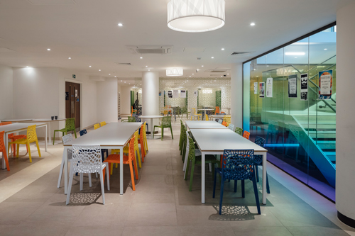Long white tables with multi coloured chairs at Cartwright gardens student accommodation.