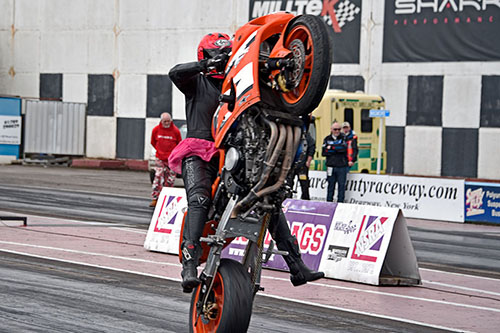 Motorcycle performing a wheelie during a drag race