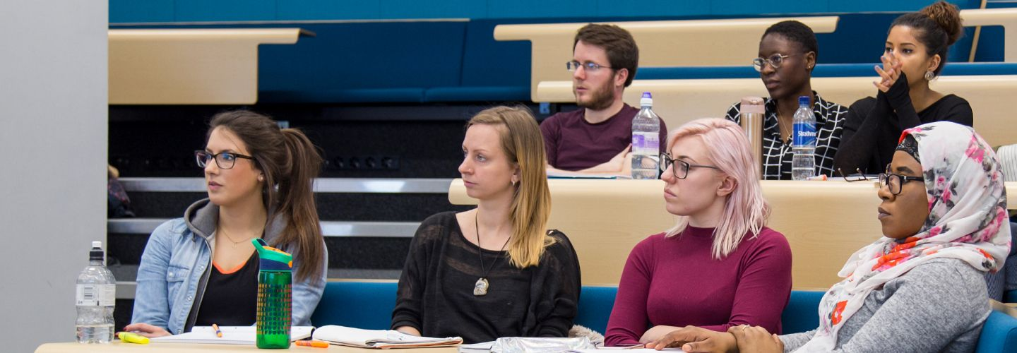 Postgraduate students seated in lecture listening