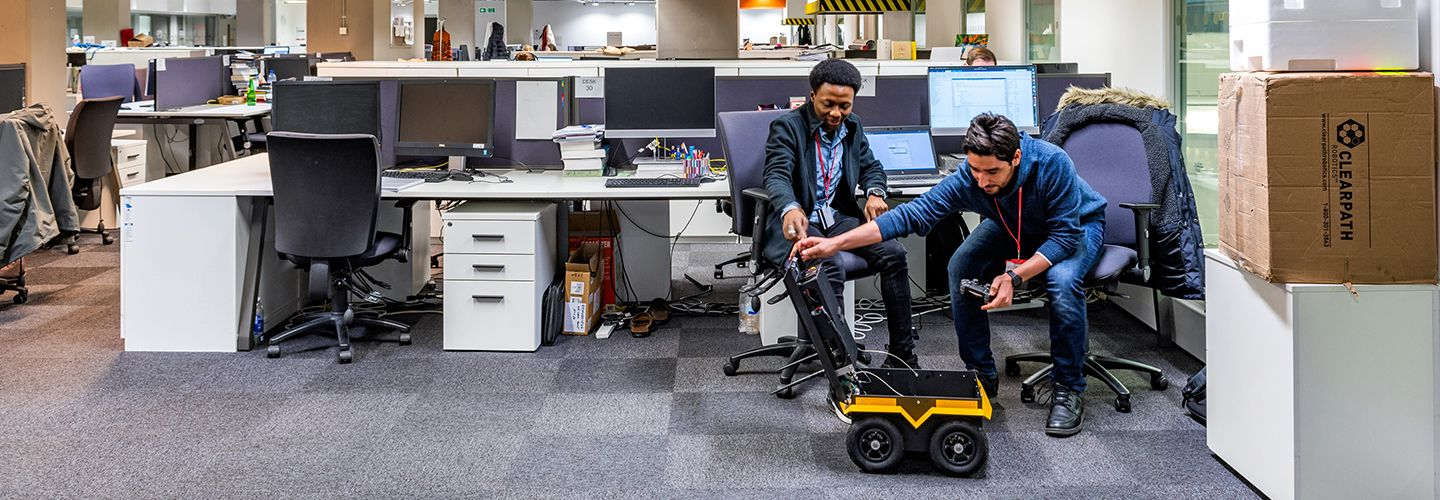 PhD students in an office looking inside Jackal robot