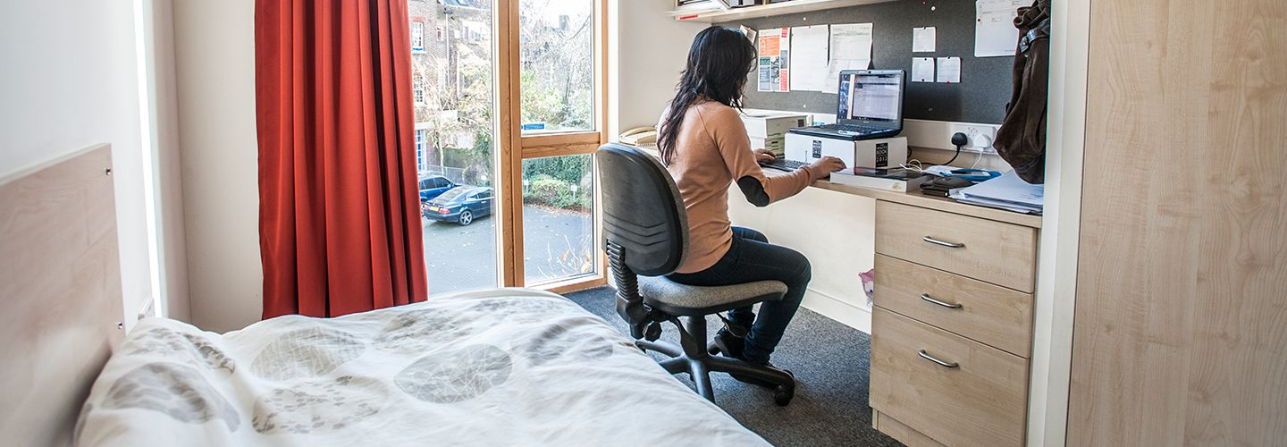 Female student at a desk in bedroom accommodation