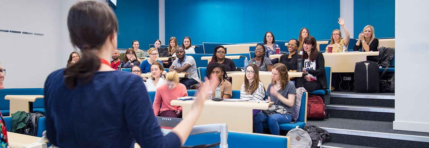 Female academic talking in front of room full of students