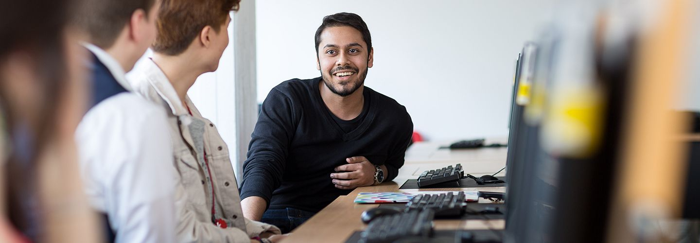 Male student smiling at other students sat next to computer screen