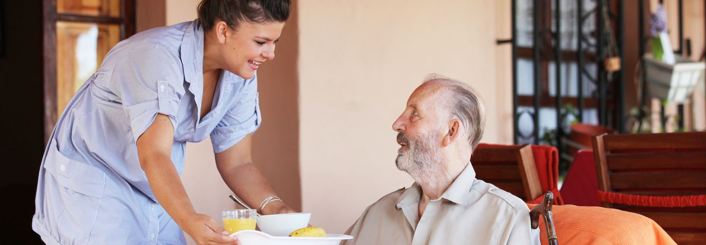 A smiling woman brings food and drink to an elderly man
