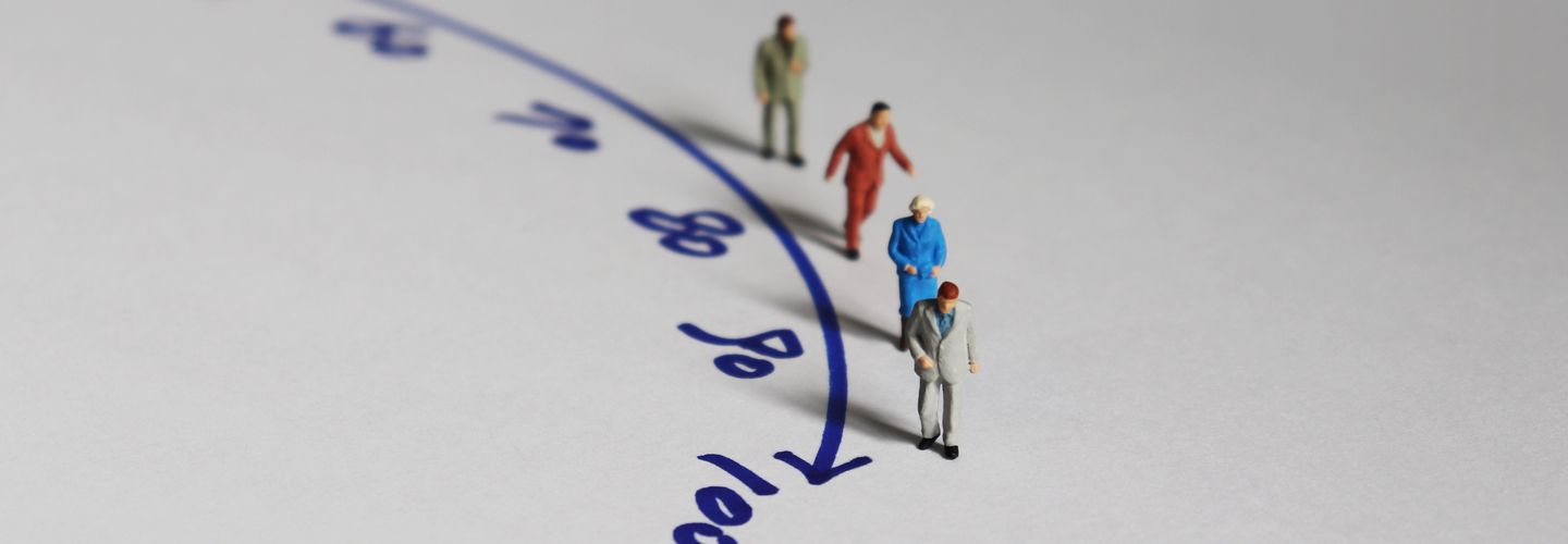 Mini figures posed along a curve line with numbers leading up to 100.