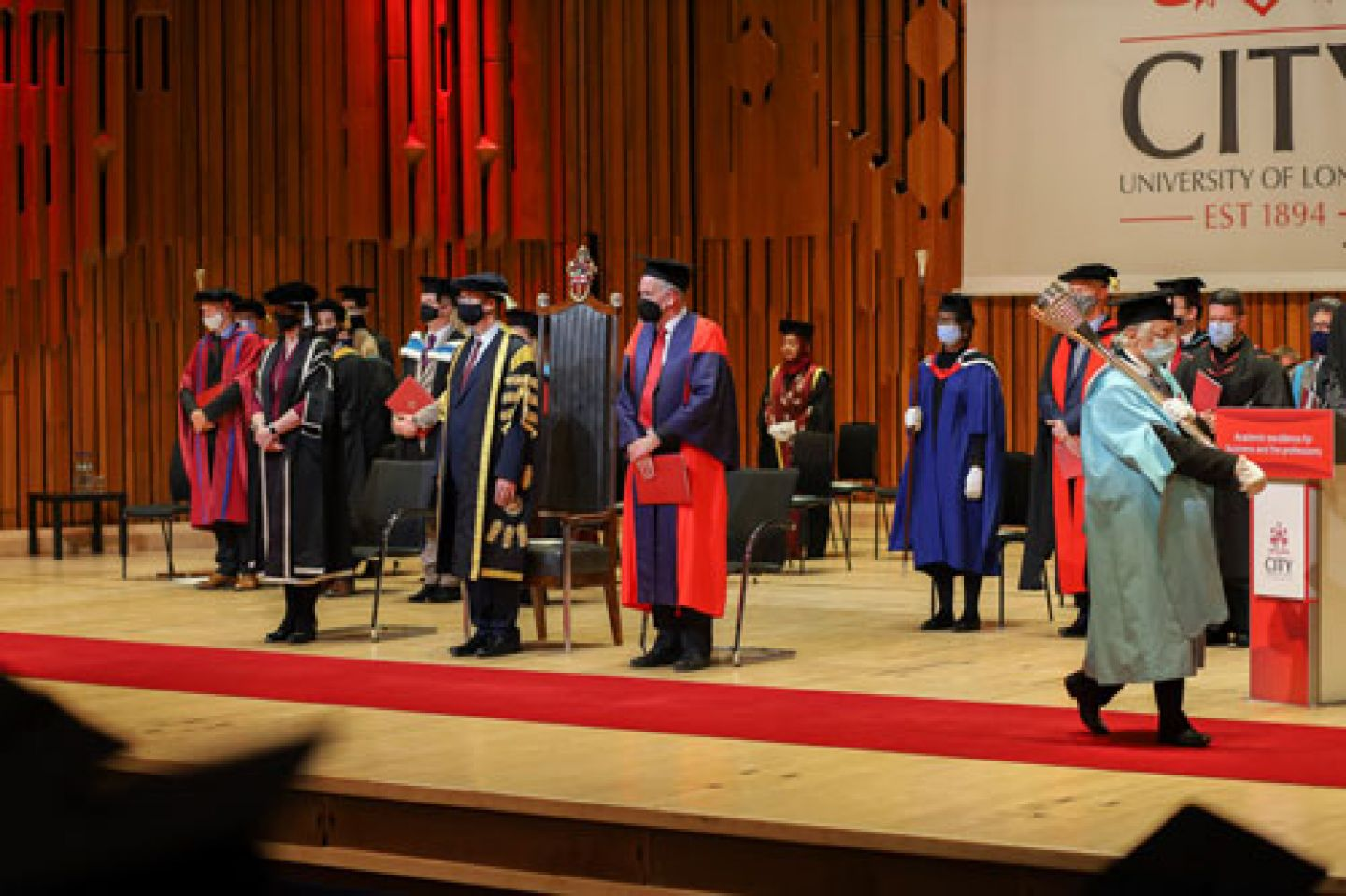 The academic procession wear face coverings on stage.