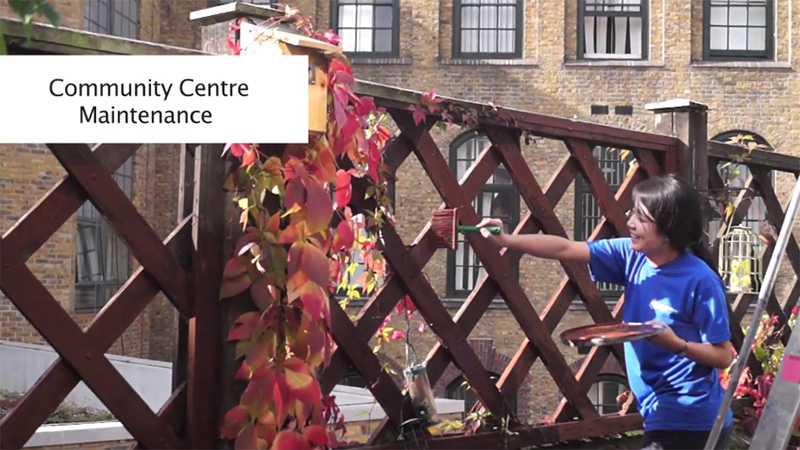 City volunteer paints a fence in video still
