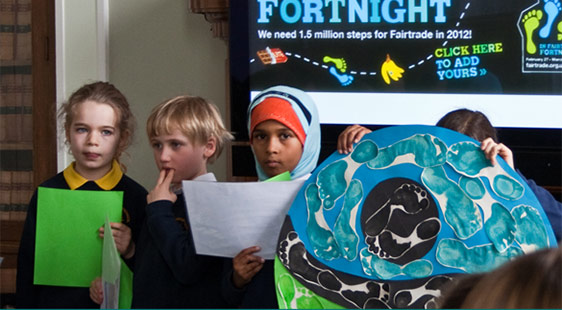 A group of young children holding Fairtrade-related items