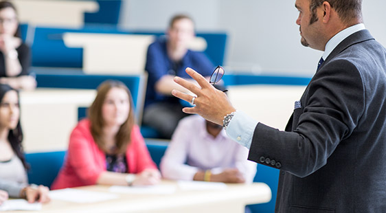 A lecturer presenting to a group of students