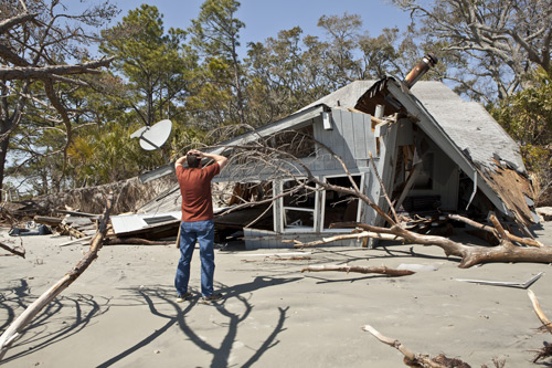 man in front of demolished house