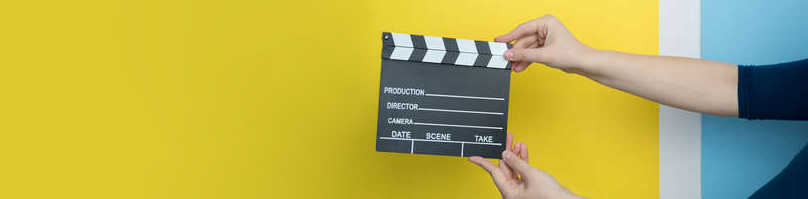 Female hands holding film clapperboard on yellow background