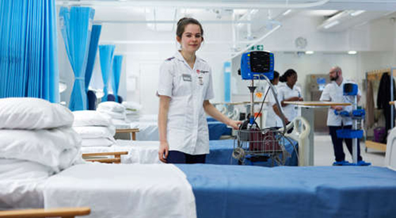 Female student nurse faces camera in City teaching ward