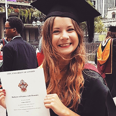 Sandra Sorensen smiling holding graduation certificate