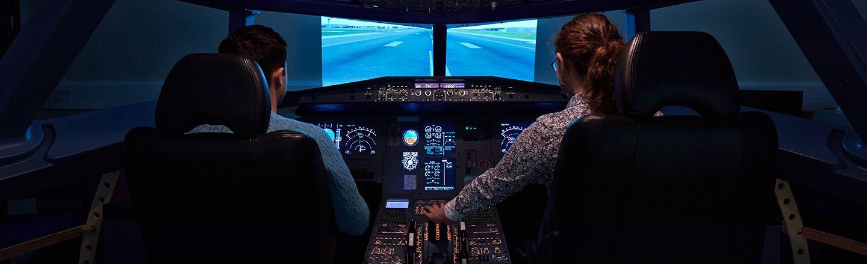 Two students inside a flight simulator