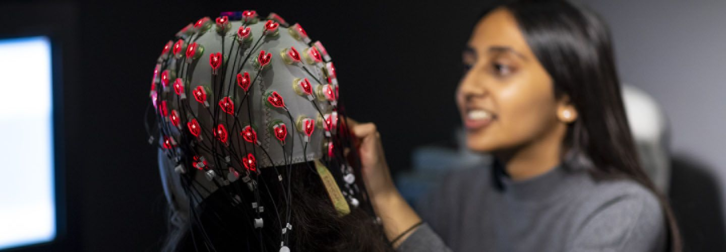 A female student applies a cap with wires to another student in the lab.