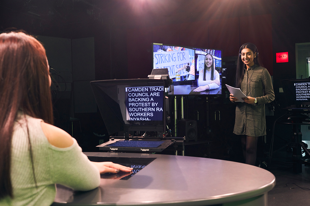 Students presenting and managing the autocue in the journalism TV studio