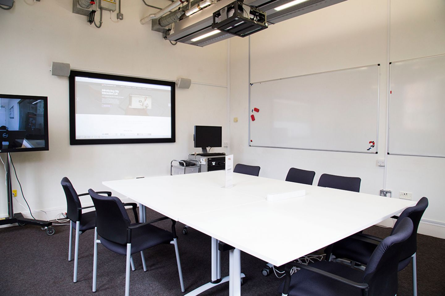 Interior of interaction lab featuring projectors and tables