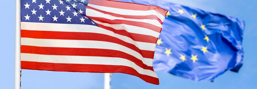 American and European union flags over a blue sky