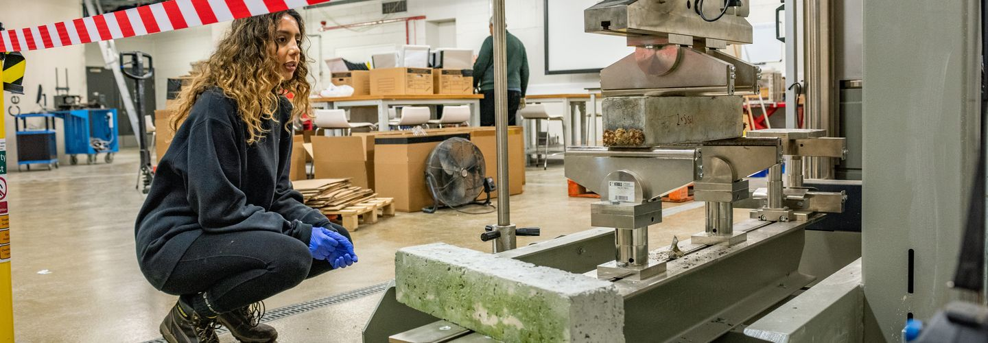 Young female third year Civil Engineering student crouches by some machinery with concrete blocks, in the Civil Engineering Labs.