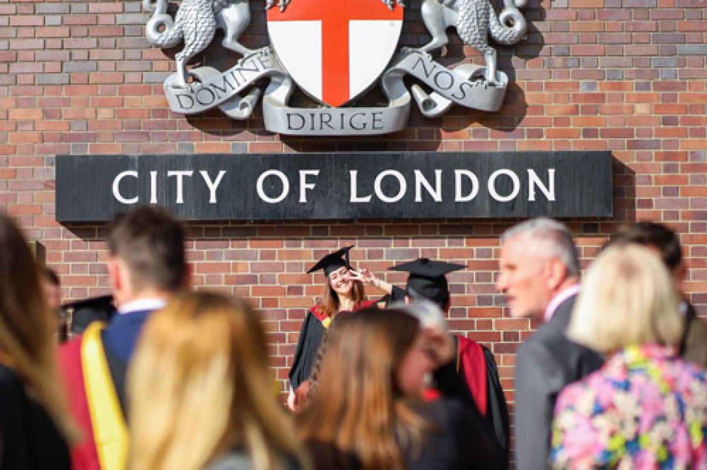 One graduate poses in front of the City of London sign.