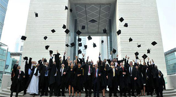 New graduates throw their mortarboards outside the DIFC in Dubai