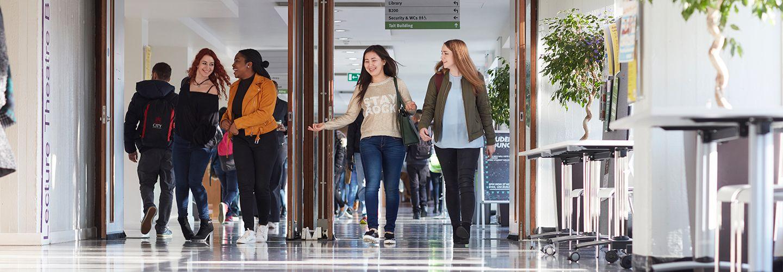 Female students walking down main university walkway