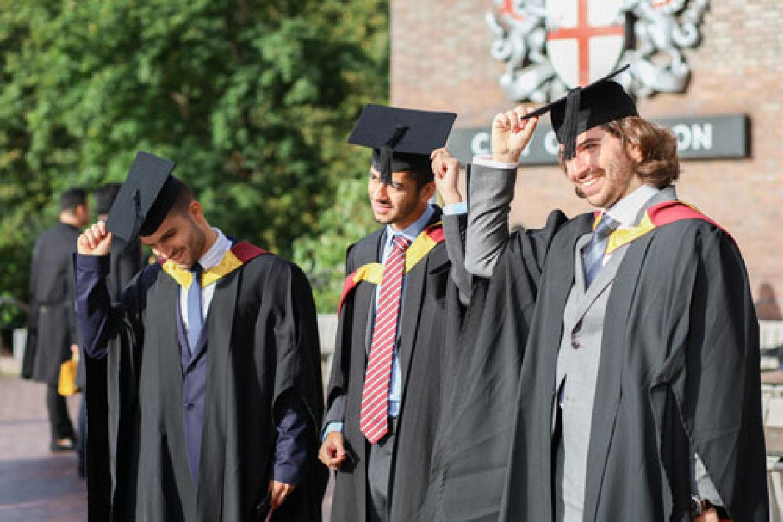 Three graduates practise doffing their caps.