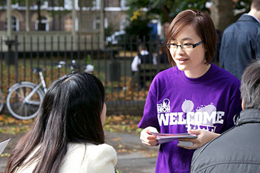 A student ambassador talks to new students wearing a purple t-shirt reading: Welcome