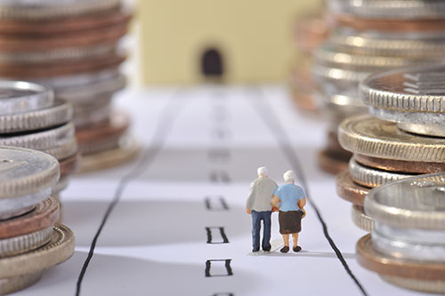 A miniature model elderly couple walk a path between towering piles of coins