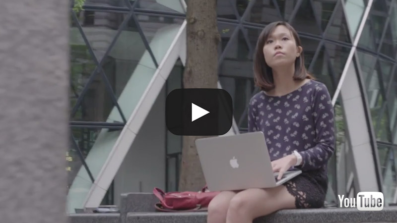 Still from a video about postgraduate study at City showing a female student with a laptop
