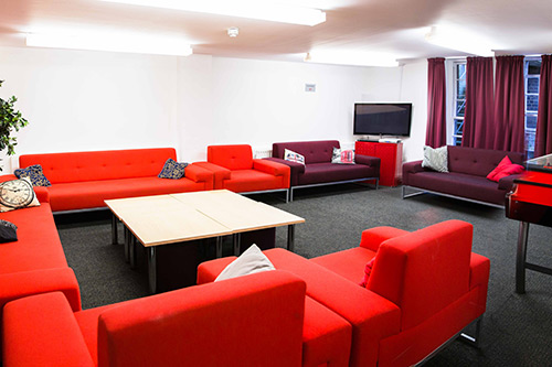 Alliance House common room with red and purple chairs and sofas, a flatscreen tv and table football.