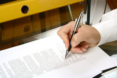 Hand holding writing pen over paper document