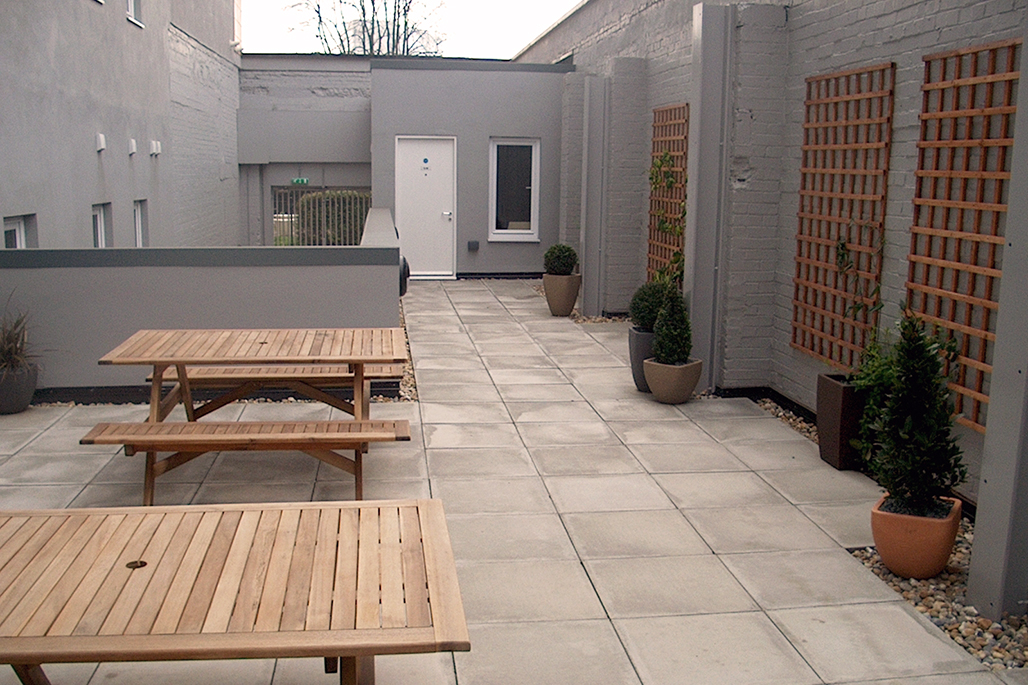 Private paved courtyard with two picnic tables, pot plants and trellises.