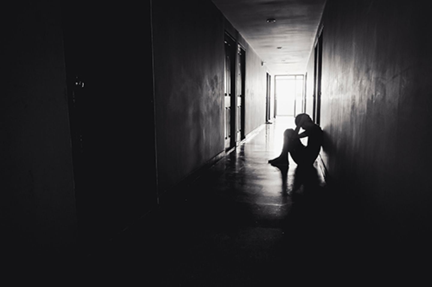 Black and white image of a silhoutted person sitting in a corridor with their head in their hands