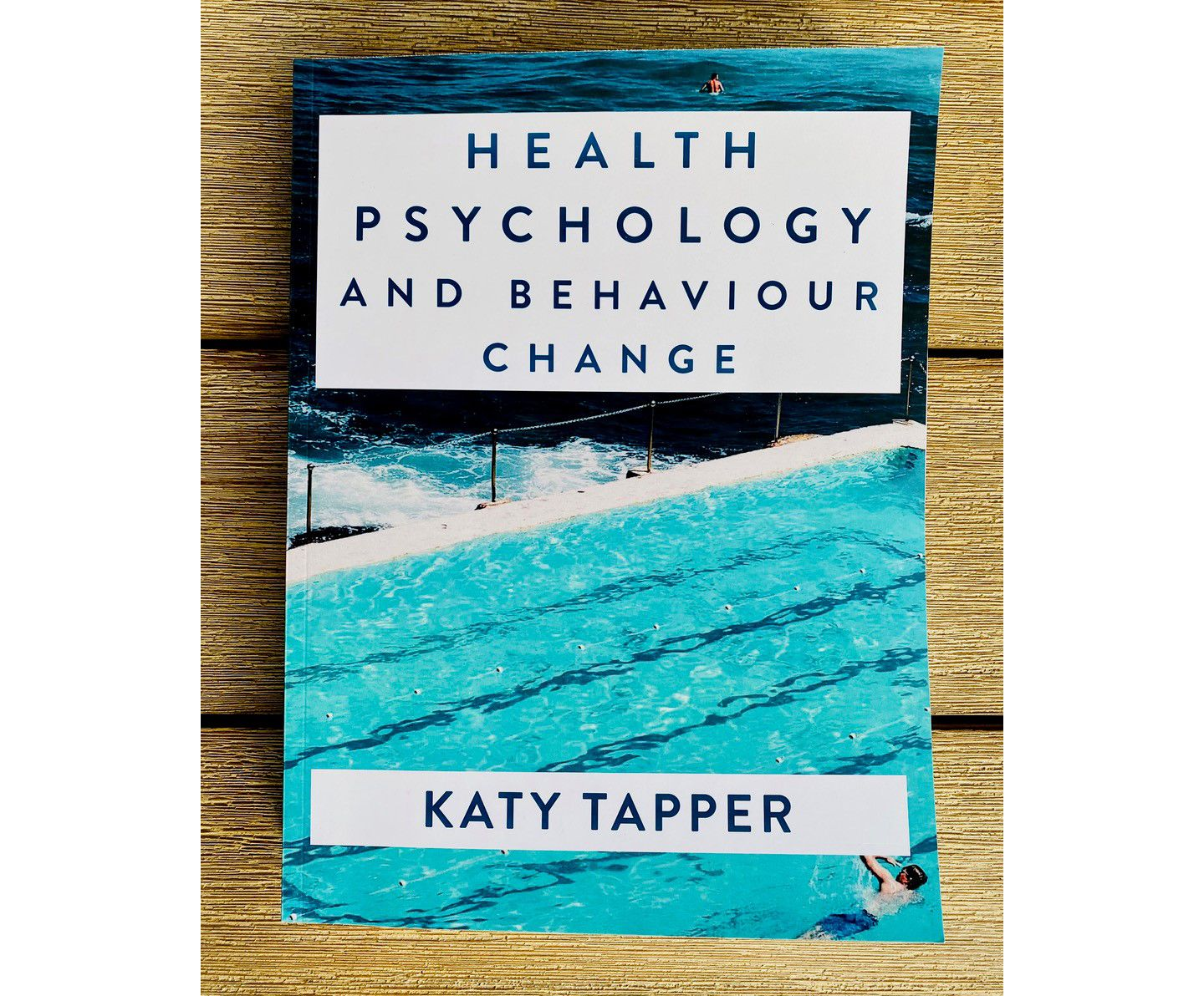 Book cover showing a swimming pool built right beside the sea. Someone is swimming in the pool, while a second person can be seen in the distance in the sea,