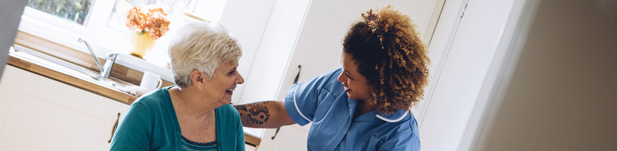 Female nurse helping an elderly patient. Saving for social care.