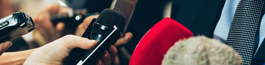 Media microphones held towards a man. Trump assault claims