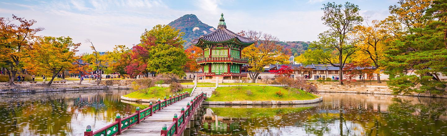 Bridge leading to Gyeongbokgung palace garden surrounded by a pond