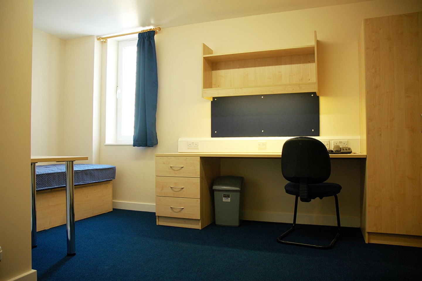 View of a studio room showing the single bed, small table, window and study area desk. The carpet and curtain are dark blue, with cream walls. The furniture is pale wood. The desk is wide, with a small chest of drawers, 4 plug sockets, pin board and overhead shelves.
